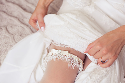 White lace garter on leg of the bride